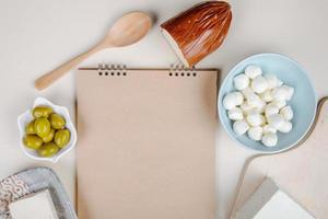 Draufsicht auf ein Skizzenbuch und verschiedene Arten von Käse-Mini-Mozzarella-Käse in einer blauen Schüssel, Feta, geräuchertem und Schnurkäse mit eingelegten Oliven auf weißem Hintergrund