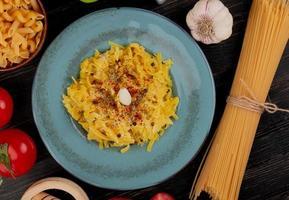 Draufsicht von Makkaroni-Nudeln in Platte mit Tomaten-Pfeffer-Knoblauch-Brecher-Knoblauch und Fadennudeln auf hölzernem Hintergrund foto