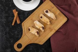 Draufsicht von Mehlplätzchen mit Erdbeermarmelade auf einem Holzbrett mit einer Tasse Kaffee und Zimtstangen auf schwarzem Hintergrund