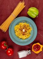 Draufsicht von Makkaroni-Nudeln in Platte mit Tomatenketchup-Salzpfeffer-Ketchup und Fadennudeln auf Bordo-Stoffhintergrund foto