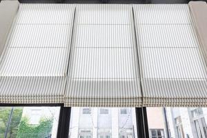 Innendekoration des grauen und weißen Vorhangs im Wohnzimmer mit Sonnenlicht