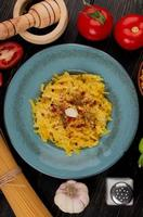 Draufsicht von Makkaroni-Nudeln in Platte mit Tomaten-Pfeffersalz-Knoblauch-Brecher-Knoblauch und Fadennudeln auf hölzernem Hintergrund foto