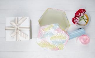 Draufsicht von Geschenkboxen und roten Farbrosen mit Rollen des Klebebandes und des rosa Bandes auf weißem hölzernem Hintergrund