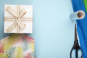 Draufsicht der Geschenkbox gebunden mit Bogen und Schere mit Rollen des bunten Papiers auf blauem Hintergrund mit Kopienraum foto