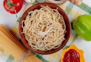 Draufsicht der Makkaroni-Nudeln in der Schüssel mit Ketchup-Knoblauchpfeffer und Fadennudeln des schwarzen Pfeffers der Tomate auf kariertem Stoff und weißem Hintergrund