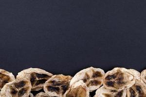 Draufsicht auf getrocknete Bananenchips, die unten auf schwarzem Hintergrund mit Kopienraum angeordnet sind foto