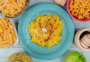 Draufsicht von Makkaroni-Nudeln in Platte mit verschiedenen Makkaronis als Penne-Spaghetti und anderen schwarzen Pfefferpfeffer herum auf hölzernem Hintergrund foto