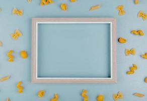 Draufsicht auf Makkaronis als Farfalle Fusilli Penne Pipe-Rigate um Rahmen auf blauem Hintergrund mit Kopierraum