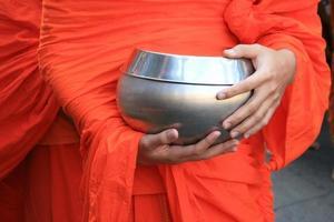 Mönch hält silberne Schüssel foto