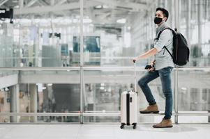 Mann trägt Maske und Rucksack am Flughafen