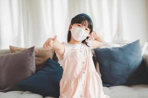 Mädchen, das Gesichtsmaske trägt, die Daumen aufgibt foto
