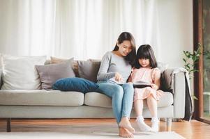 Mutter und Tochter lesen ein Buch foto