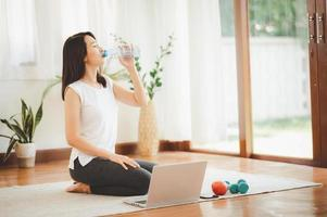 Frau, die Wasser während des virtuellen Trainings trinkt