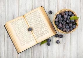 Draufsicht der kleinen sauren blau-schwarzen Schlehen auf einem Eimer mit Blättern auf einem grauen hölzernen Hintergrund foto