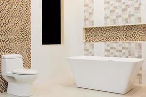 luxuriöses weißes Badezimmer mit weißen Fliesen, Spiegel, Waschbecken und weißer Badewanne. Konzept der Entspannung.