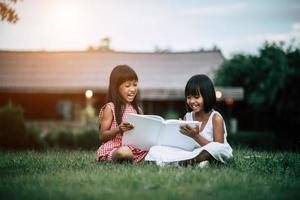 zwei kleine Mädchen im Park auf dem Rasen, die ein Buch lesen und lernen