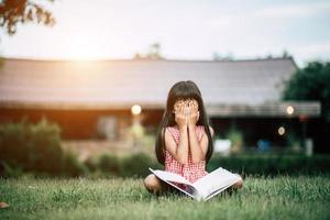 junges Mädchen, das im Garten außerhalb ihres Hauses liest