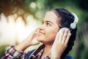 junges glückliches Mädchen, das Musik mit ihren Kopfhörern hört