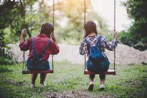zwei junge Mädchen sitzen zusammen auf einer Schaukel