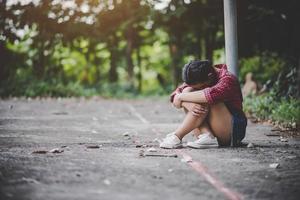 trauriges Mädchen, das in einem Park sitzt foto