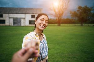 Frau geht und hält die Hand ihres Freundes, der ihr folgt foto