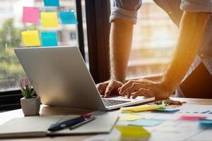 Mann mit einem Laptop in einem Heimbüro foto