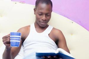 Mann liest mit einer Tasse Kaffee im Bett foto
