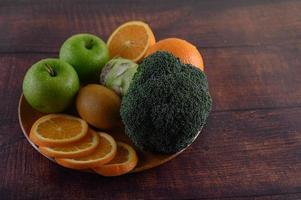 Orangenscheiben mit Apfel, Kiwi und Brokkoli auf einem Holzteller