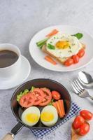 gekochte Eier, Karotten und Tomaten mit Löffel und Kaffeetasse