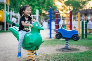 asiatisches kleines Mädchen spielt gerne auf einem Kinderspielplatz