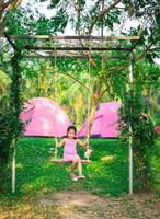 kleines Mädchen in einem rosa Kleid, das auf einer Schaukel beim Zelten sitzt