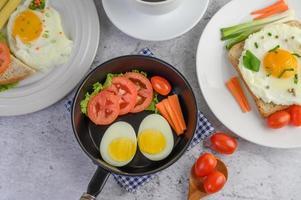 gekochte Eier, Karotten und Tomaten in einer Pfanne mit Tomaten