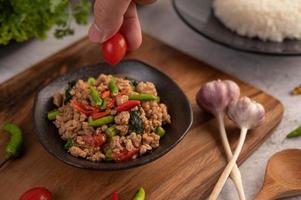 würziger gehackter Schweinefleischsalat mit Reis, Chili und Tomaten auf einem schwarzen Teller