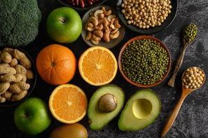 Hülsenfrüchte und Früchte auf dunklem Hintergrund