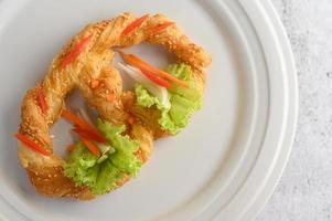 Brezel auf einem weißen Teller mit Salat und Karotten foto