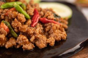 würziger gehackter Schweinefleischsalat mit Reis, Chili und Tomaten in einem schwarzen Teller
