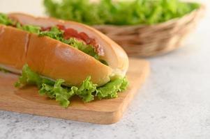 Hotdog mit Salat auf Holzschneidebrett foto