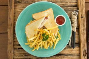 Schinken-Käse-Sandwich mit Pommes Frites auf blauem Teller