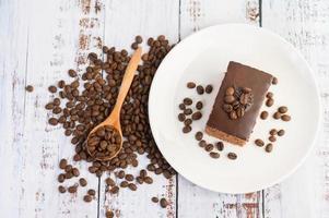 Schokoladenkuchen auf einem weißen Teller und Kaffeebohnen