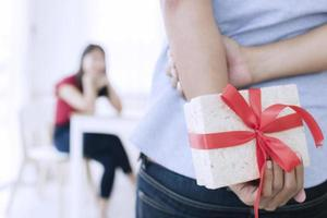 Person, die ein Geschenk hinter ihrem Rücken hält foto