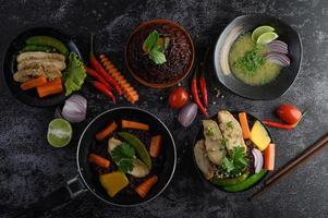 verschiedene Gerichte von Gemüse, Fleisch und Fisch auf einem schwarzen Steinhintergrund