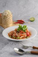 thailändischer Papayasalat auf einem weißen Teller mit Klebreis, Chili, Löffel und Gabel foto