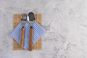 Löffel und Gabel auf blauen und weißen Taschentüchern foto