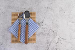 Löffel und Gabel auf blauen und weißen Taschentüchern