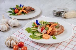 Schweinesteak mit Tomaten, Karotten, roten Zwiebeln, Pfefferminze, Schmetterlingserbsenblüte und Limette foto