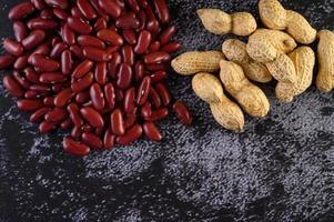 Erdnüsse und rote Bohnen auf einem schwarzen Zementbodenhintergrund