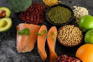 Hülsenfrüchte, Brokkoli, Obst und Lachs auf einem schwarzen Zementhintergrund
