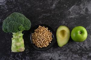 Brokkoli, Apfel, Avocado und Bohnen auf einem schwarzen Zementbodenhintergrund