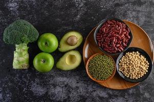 Brokkoli, Apfel und Avocado mit Bohnen auf einem schwarzen Zementbodenhintergrund