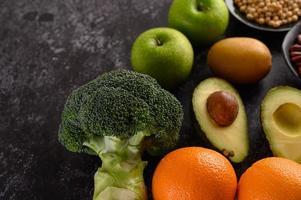 Brokkoli, Apfel, Orange, Kiwi und Avocado auf einem schwarzen Zementbodenhintergrund